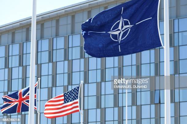 The Union Jack flag the US national flag and the NATO flag flutter in the wind during the NATO summit ceremony at the NATO headquarters in Brussels...