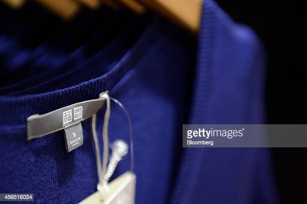 The Uniqlo logo is displayed on the label of a sweater for sale inside a Uniqlo store operated by Fast Retailing Co in Tokyo Japan on Thursday Oct 2...