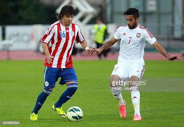 the United Arab Emirates' forward Ali Mabkhout and Paraguay's midfielder Oscar Romero vie for the ball during the FIFA friendly football match...