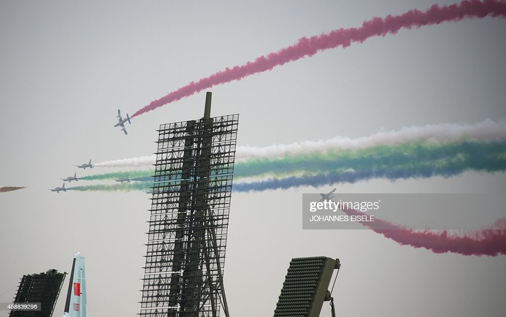 The United Arab firstst Aerobatic team performs in their MB339A jets next to a Chinese Radar system on display at the Airshow China 2014 in Zhuhai...