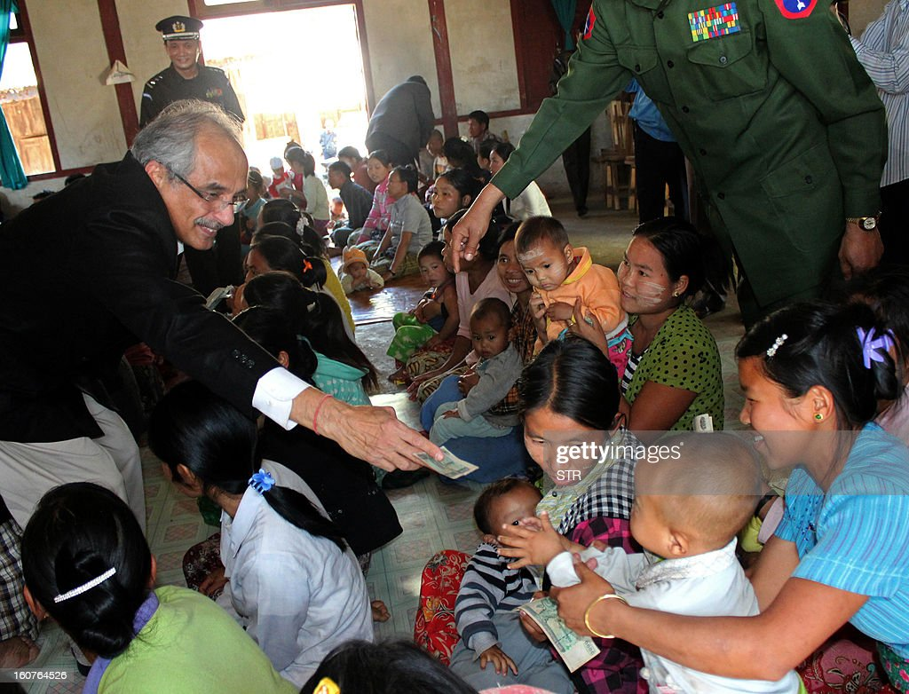 The United Nations secretary-general's special adviser on Myanmar,Vijay Nambiar (L), give money to an ethnic Kachin family during his visit to an Internally Displaced People's (IDP) camp in a government controlled area at Myitkyinar village in Kachin state on February 5, 2013. The Myanmar government last month announced a unilateral ceasefire with the Kachin but the fighting continued, with the government army capturing a key outpost as it edged closer to the rebels' headquarters near the Chinese border. AFP PHOTO/ STR