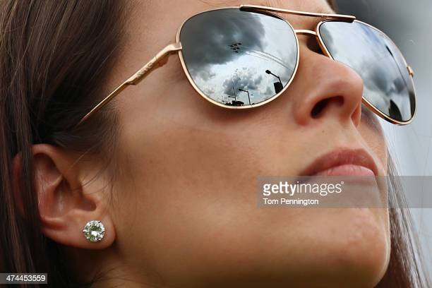 The United States Air Force Thunderbirds are reflected in the sunglasses of Danica Patrick driver of the GoDaddy Chevrolet as they fly over during...