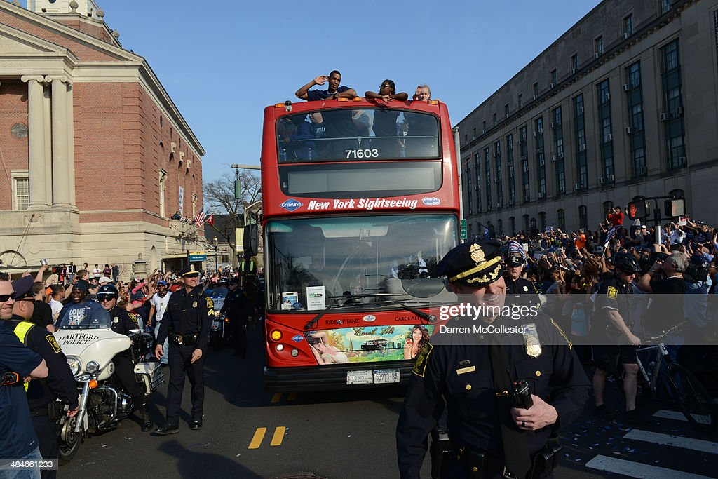 The University of Connecticut men's basketball team ride in a victory parade to celebrate their national championship April 13, 2014 in Hartford, Connecticut. This year was the second time both the men's and women's Uconn basketball teams have won national championships in the same year.