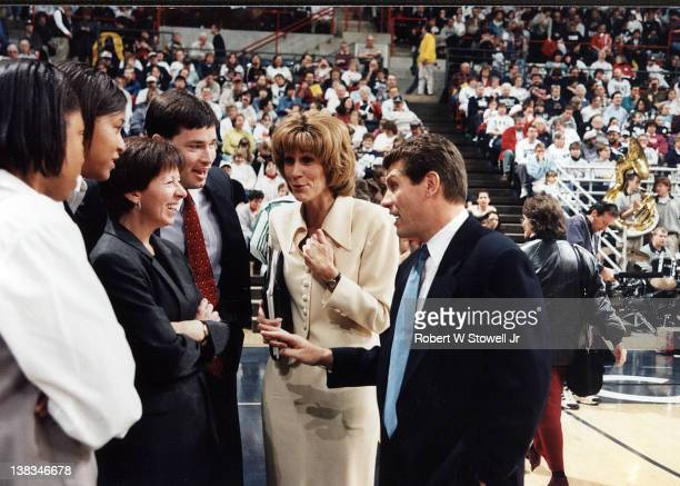 The University of Connecticut women's basketball coaches Geno Auriemma and Chris Dailey talk with Notre Dame coach Muffet McGraw before a game Storrs...