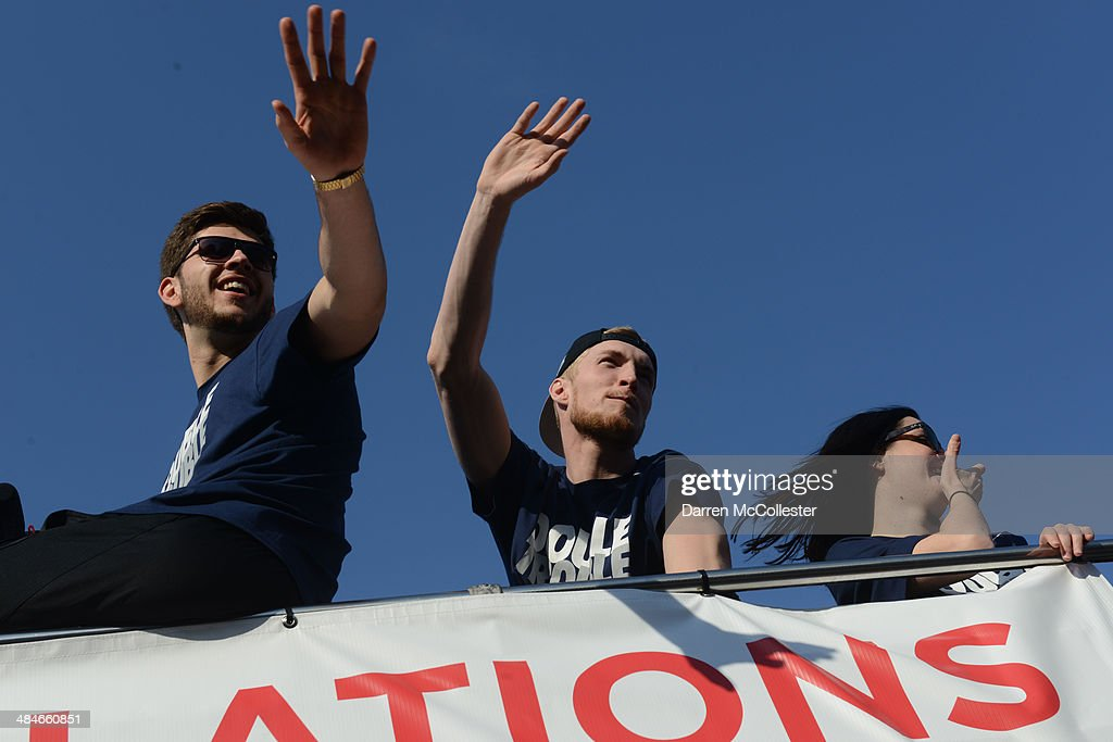 The University of Connecticut's Leon Tolksdorf (L) and Niels Giffey ride in a victory parade to celebrate their team's national championship April 13, 2014 in Hartford, Connecticut. This year was the second time both the men's and women's Uconn basketball teams have won national championships in the same year.