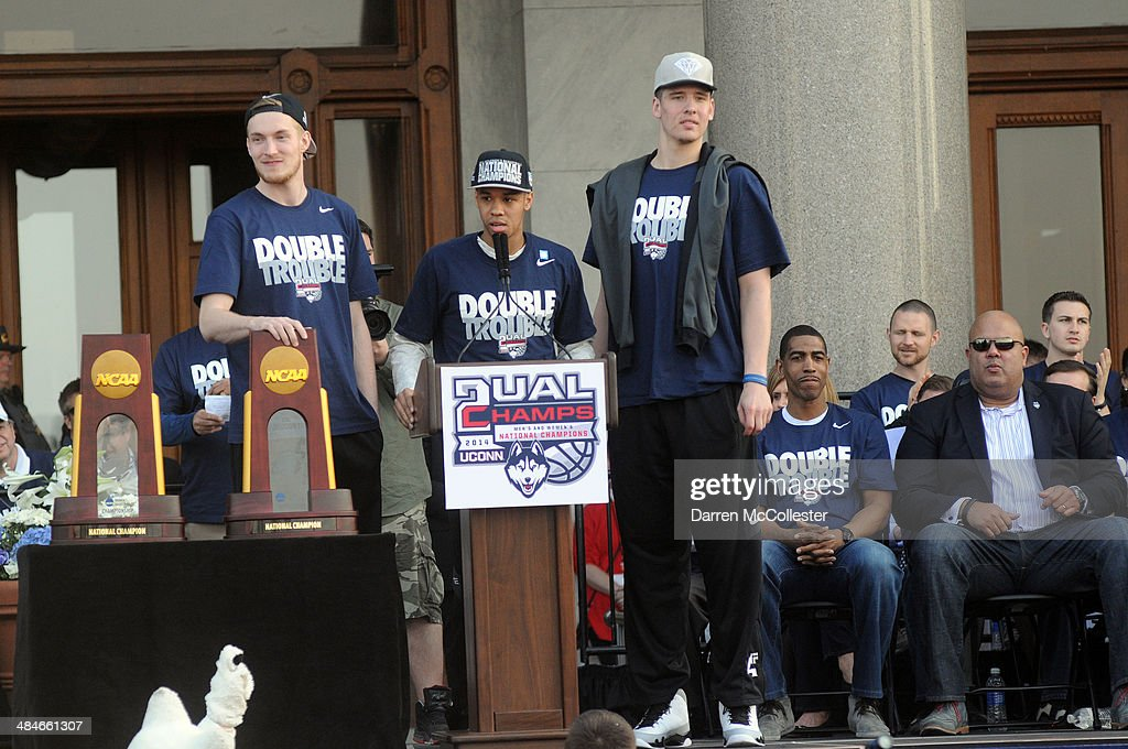 The University of Connecticut's Shabazz Napier (C), Niels Giffey (L) and Tyler Olander, and head coach Kevin Ollie stand on stage during a rally to celebrate their national championship April 13, 2014 in Hartford, Connecticut. This year was the second time both the men's and women's Uconn basketball teams have won national championships in the same year.