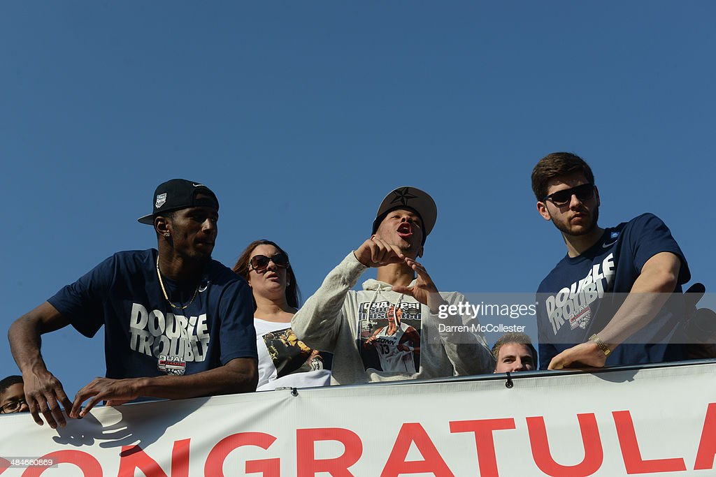 The University of Connecticut's Shabbaz Napier (C), DeAndre Daniels (L) and Leon Tolksdorf ride in a victory parade to celebrate their team's national championship April 13, 2014 in Hartford, Connecticut. This year was the second time both the men's and women's Uconn basketball teams have won national championships in the same year.