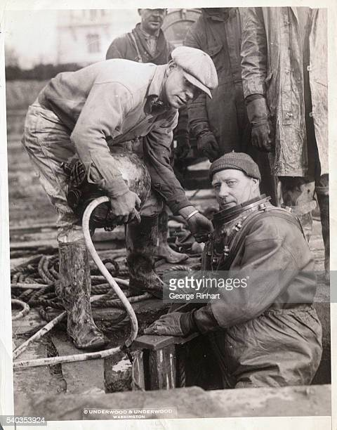 The unusual sight of a deep sea diver in all his weird paraphernalia emerging from a hole in the ground in the heart of the Capitol City took place...