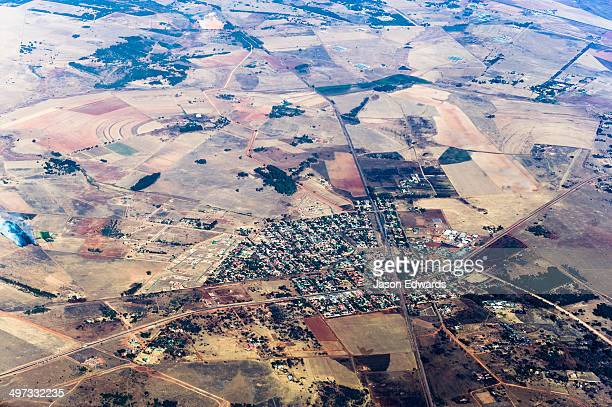 The urban sprawl of a village surrounded by a vast plain dotted with agricultural land and farms.