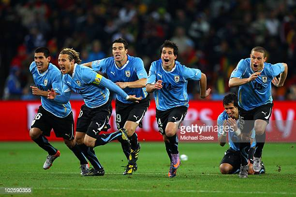 The Uruguay team celebrate as Sebastian Abreu of Uruguay scores the winning penalty in a penalty shoot out during the 2010 FIFA World Cup South...