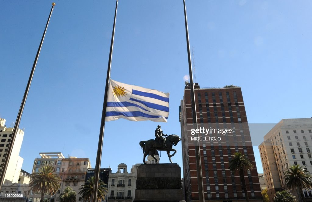 The Uruguayan flag flutters at half-mast at the Independencia square in Montevideo, on March 6, 2013, during the three-day national mourning for the death of Venezuelan President Hugo Chavez on the eve. Condolences poured in Wednesday from world leaders who had found common cause with Venezuela's Hugo Chavez in his 14-year campaign to galvanize the Latin American left and defy US 'imperialism.' AFP PHOTO/Miguel ROJO