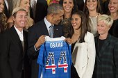 The US 2015 Women's World Cup Team's Abby Wambach and Carli Lloyd present US President Barack Obama with a team jersey during an event honoring them...