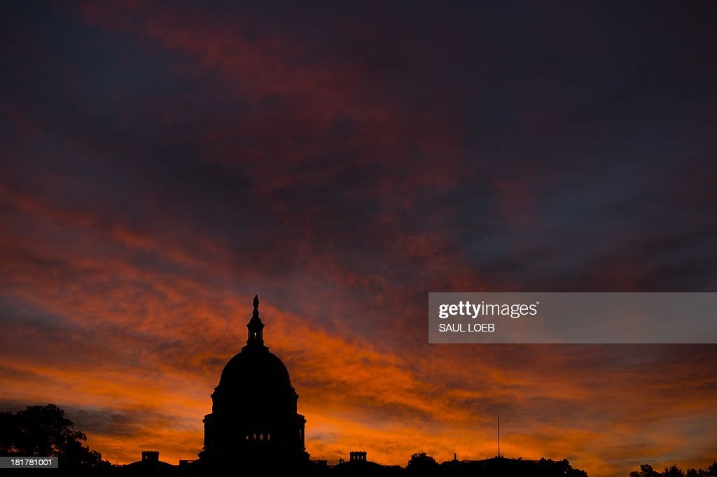The US Capitol dome is seen at sunrise over Washington, DC, September 25, 2013. The US Senate faces a Sunday showdown over whether to keep government running, but bickering over US President Barack Obama's signature health care law is bringing federal agencies dangerously close to a shutdown. A fractured Congress is struggling to approve a stopgap spending bill that keeps government doors open after the current fiscal year ends next Monday. AFP PHOTO / Saul LOEB