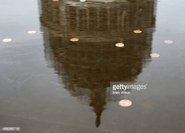 The US Capitol is reflected in a fountain full of coins on the plaza November 4 2014 in Washington DC Today Americans head to the polls to cast their...