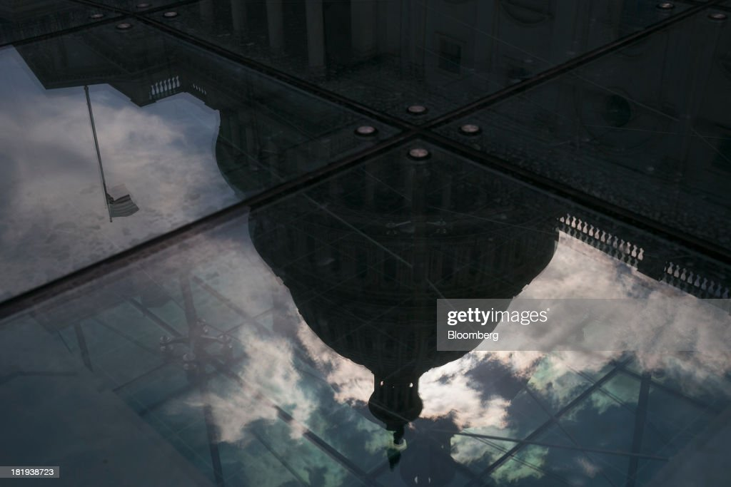 The U.S. Capitol is reflected in Washington, D.C., U.S., on Thursday, Sept. 26, 2013. The Senate is accelerating debate on a bill that would avert a U.S. government shutdown as Senate Republicans sought to buy time for their House counterparts to take another swipe at President Barack Obama's health-care law. Photographer: Andrew Harrer/Bloomberg via Getty Images