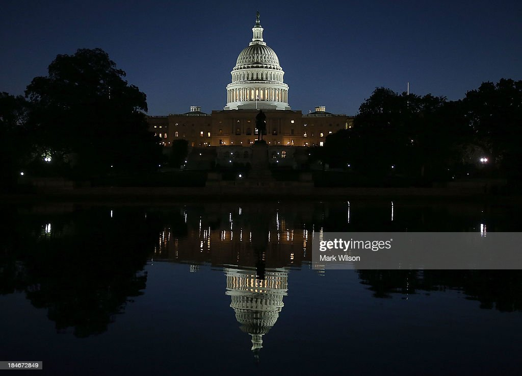 The U.S. Capitol is reflected in water, October 15, 2013 in Washington, DC. With the government shutdown going into the fifttenth day and the deadline for raising the debt ceiling fast approaching, Democrats and Republicans may come to an agreement soon on passing a budget.