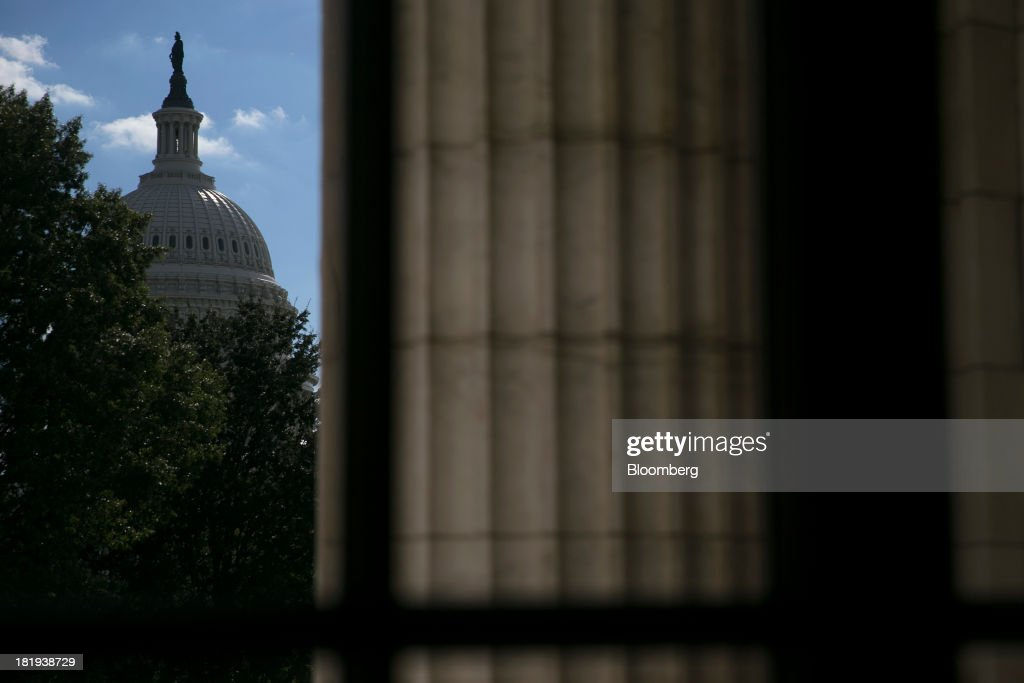The U.S. Capitol is seen past a pillar of the Russell Senate Office Building in Washington, D.C., U.S., on Thursday, Sept. 26, 2013. The Senate is accelerating debate on a bill that would avert a U.S. government shutdown as Senate Republicans sought to buy time for their House counterparts to take another swipe at President Barack Obama's health-care law. Photographer: Andrew Harrer/Bloomberg via Getty Images