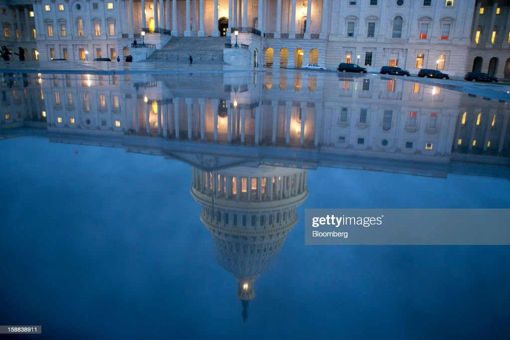The U.S. Capitol is seen reflected in Washington, D.C., U.S., on Monday, Dec. 31, 2012. The U.S. House of Representatives doesn't plan any votes on the federal budget tonight, meaning that Congress for now will fail to avert $600 billion in tax increases and spending cuts set to start at midnight. Photographer: Andrew Harrer/Bloomberg via Getty Images