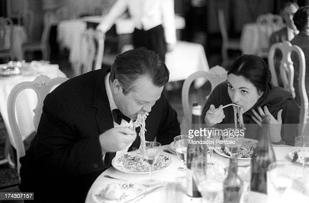 the US film director Orson Welles and his third wife the Italian actress Paola Mori born the countess Paola Di Girifalco eat a plate of spaghetti...