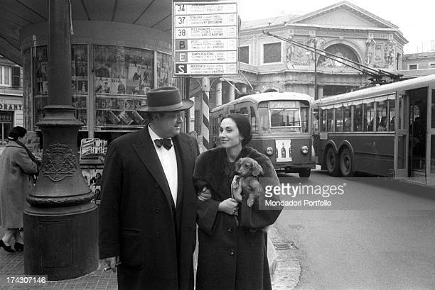 The US film director Orson Welles with a cigar in his mouth and a large hat on his head walks arm in arm with his third wife the Italian actress...