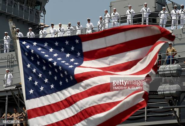 The US Flag blows in the wind as Sailors and Marines stand on the deck of the USS Bataan as it arrives into Pier 88 during the 'Parade of Ships'...