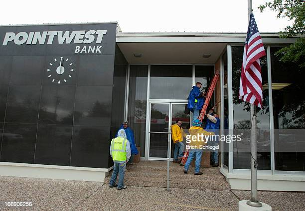 The US flag flies at half staff as workers with Gate Precast cover a broken window at Pointwest Bank with plywood on April 18 2013 in downtown West...