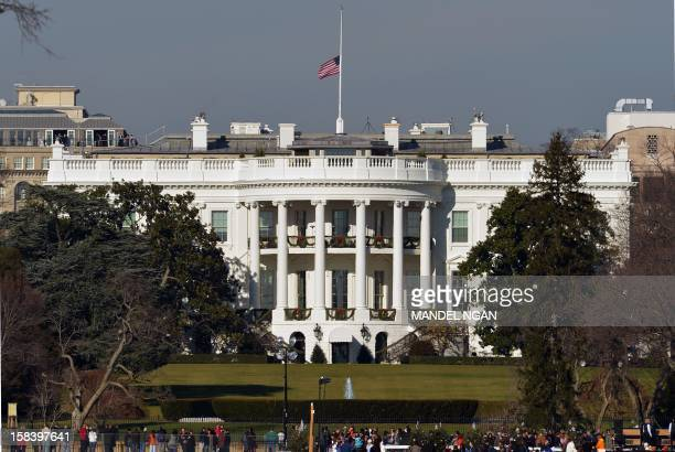 The US flag flies at halfstaff above the White House on December 15 2012 in Washington Twentyseven people including the shooter were killed on...