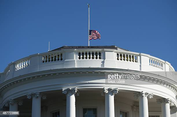 The US flag flies at halfstaff at the White House in Washington DC September 11 to mark the 14th anniversary of the 9/11 attacks on the United States...