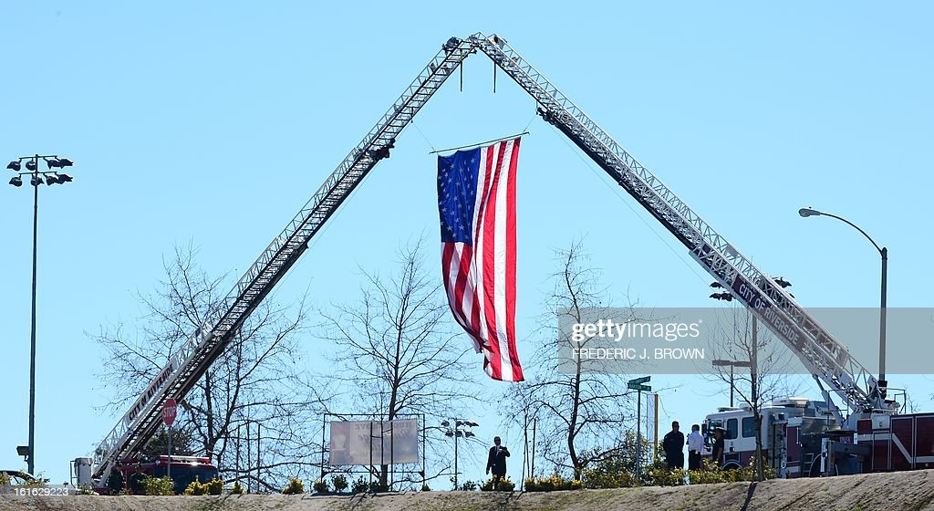 The US flag flies near the Grove Community Church where a memorial service for slain Riverside police officer Michael Crain was held in Riverside, California, on February 13, 2013. Law enforcement personnel from across the state, including local dignitaries, military veterans, colleagues, friends and loved ones of Crain gathered to pay their final respects to the policeman killed last week in what the city's police chief described as a 'cowardly ambush.'' Crain was fatally shot February 7 when he and his partner ran afoul of fugitive Christopher Jordan Dorner. AFP PHOTO / Frederic J. BROWN