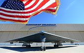 The US flag flutters in the wind beside a B2 Stealth Bomber at the Palmdale Aircraft Integration Center of Excellence in Palmdale California on July...
