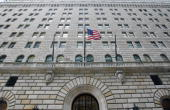 The US flag hangs on the facade of the Federal Reserve Bank of New York headquarters in New York US on Monday Dec 15 2008 The Federal Reserve Bank of...