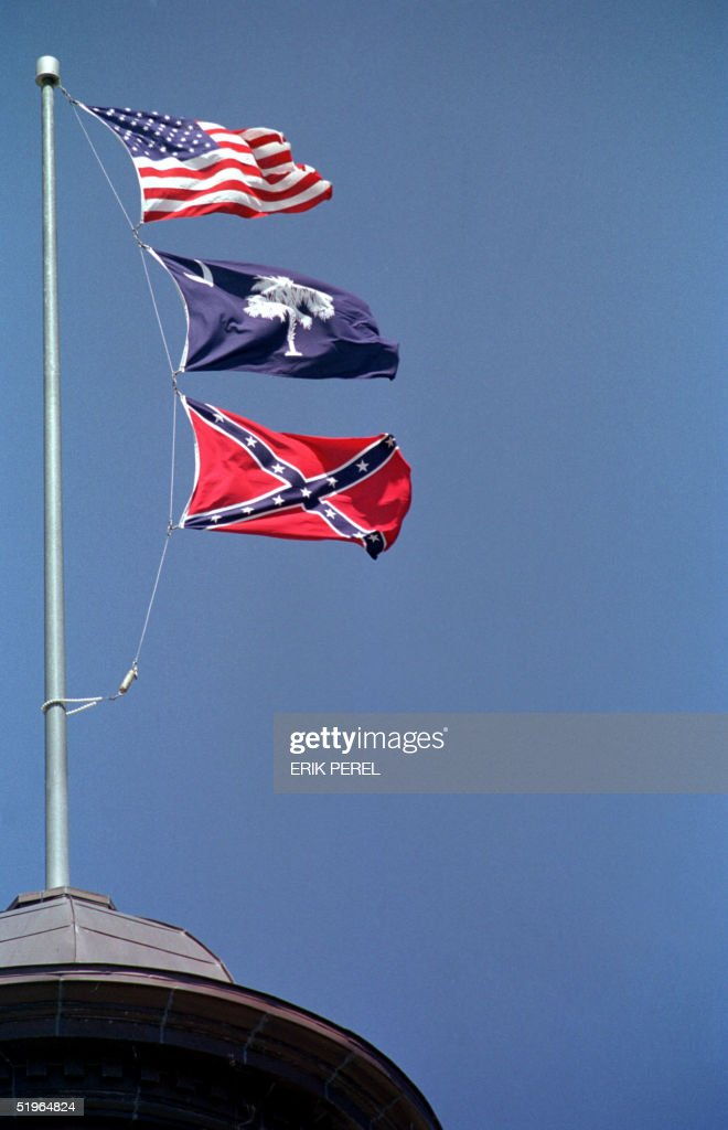 The US flag (top), the state flag of South Carolina (middle) and the Confederate flag (bottom) fly atop the capitol building 06 April 2000 in Columbia, SC. The 'Get in Step with the People of South Carolina' march, led by Charleston, SC, mayor Joe Riley, started in Charleston 02 April 2000 and proceeded approximately 120 miles to the captial of Columbia to protest the Confederate flag's place above the capitol building.