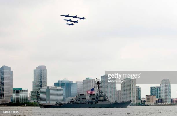 The US Navy Blue Angels fly in formation as they pass over the USS Donald Cook on the Hudson River during the Parade of Ships for the start of Fleet...