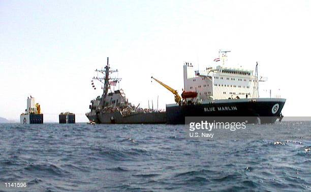 The US Navy guided missile destroyer USS Cole is lifted from the water by the Norwegian heavy transport ship Blue Marlin October 30 2000 in the Gulf...