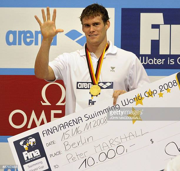 The US' Peter Marshall celebrates on the podium with his gold medal and a cheque after setting a new world record in the men's 100m backstroke race...