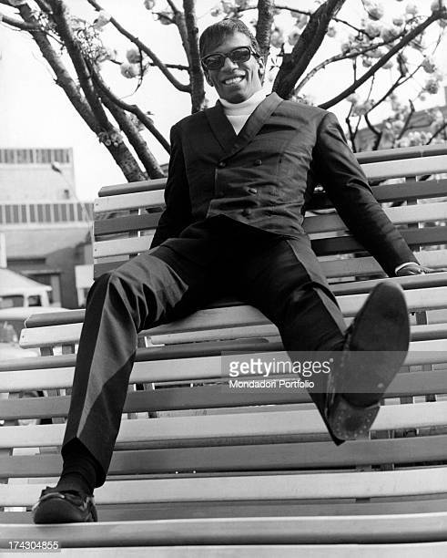 The US singer Rocky Roberts born Charles Roberts playfully poses on a park bench in front of a trade centre in Milan in Italy his career as a singer...