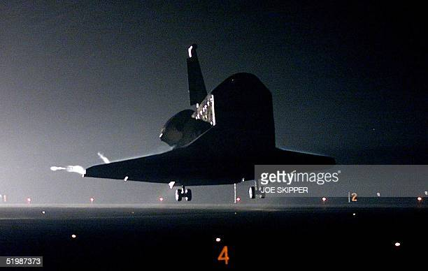 The US space shuttle Columbia glides down over the runway 33 moments before landing at the Kennedy Space Center in Florida 12 March 2002 Columbia and...