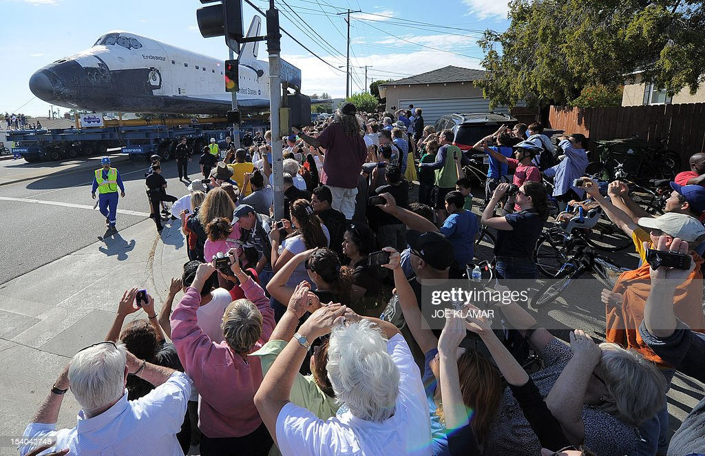 The US Space Shuttle Endeavour is moved from Westchester Square to Randy's Donuts during its final ground journey in Los Angeles, California on October 12,2012. Over the next two days, the 170,000-pound (77,272 kg) shuttle will travel at no more than 2 mph (3.2 km per hour) along a 12-mile (19km) route from LAX to it's final home at the California Science Center. NASA Space Shuttle Program ended in 2011 after 30 years and 135 missions. AFP PHOTO/JOE KLAMAR