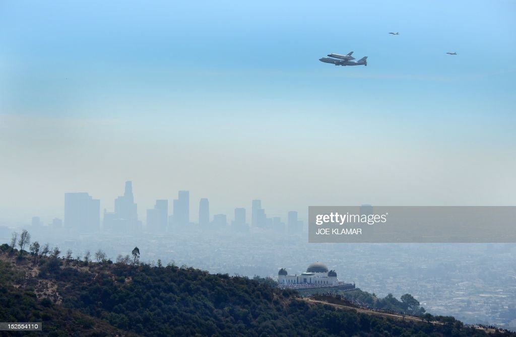 The US space shuttle Endeavour, mounted atop NASA's modified Boeing 747, flies near the Griffith Park Observatory in Los Angeles on its final flight, September 21, 2012. The retired space shuttle is spending it's last day in the air on a 5-hour flyover before landing at the Los Angeles International Airport, where it will stay for a few weeks before taking a slow-speed land journey across town through neighborhoods to its final museum home, the California Space Center.