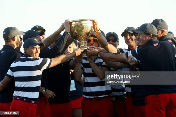 The US Team celebrates with the trophy after they defeated the International Team 19 to 11 in the Presidents Cup at Liberty National Golf Club on...
