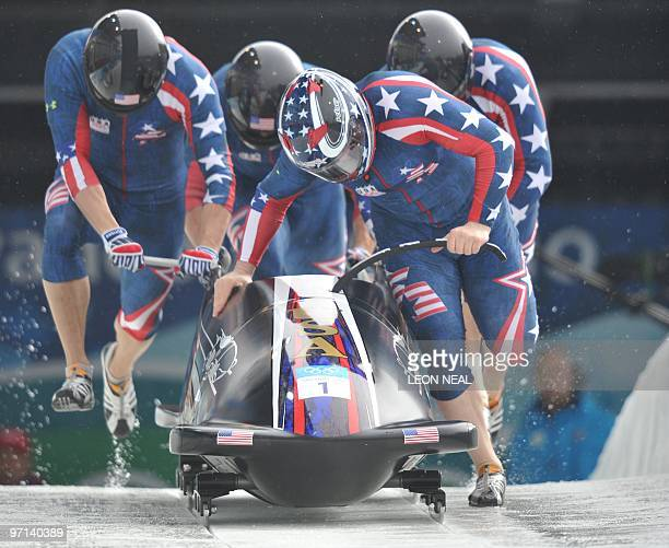 The USA1 fourman bobsleigh team piloted by Steven Holcomb start heat 3 of the 4man bobsleigh event at the Whistler sliding centre during the...