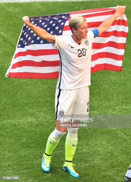 The USA's Abby Wambach celebrates holding the US national flag after defeating Japan in the 2015 FIFA Women's World Cup final at BC Place Stadium in...