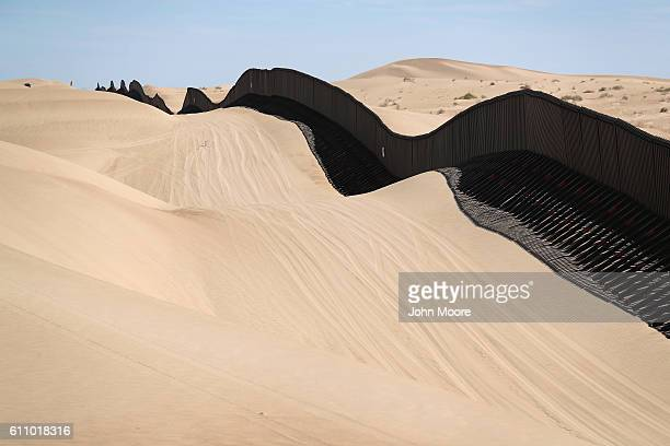 The USMexico border fence snakes over sand dunes on September 28 2016 in the Imperial Sand Dunes recreation center California Without daily removal...