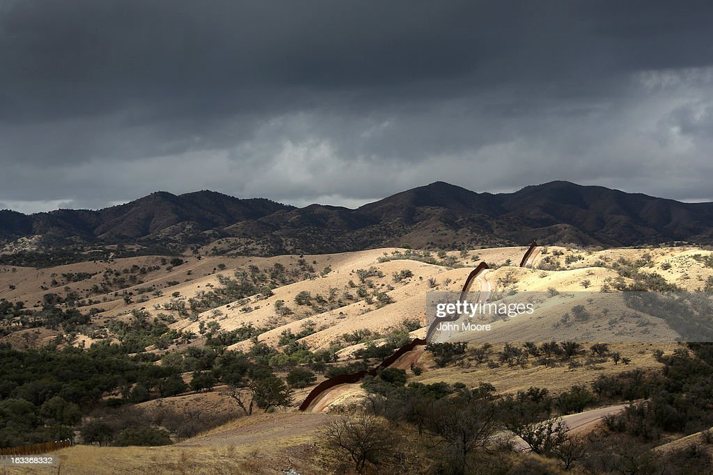 The U.S.-Mexico border fence stretches into the countryside on March 8, 2013 near Nogales, Arizona. U.S. Border Patrol agents in Nogales say they have seen a spike in immigrants crossing into the United States from Mexico in the last week.