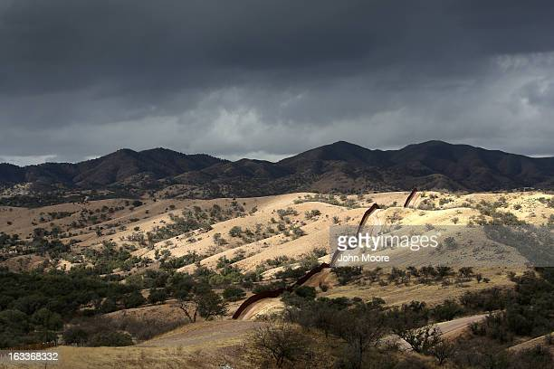 The USMexico border fence stretches into the countryside on March 8 2013 near Nogales Arizona US Border Patrol agents in Nogales say they have seen a...