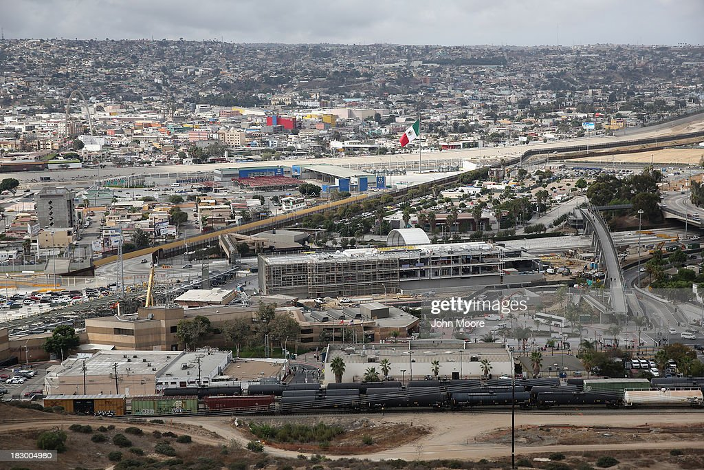 The U.S.-Mexico border fence stretches through the port of entry in Mexico (L), on October 3, 2013 at the San Ysidro, California. While hundreds of thousands of government workers were furloughed due to the federal shutdown, thousands of Border Patrol agents, air-traffic controllers, prison guards and other federal employees deemed 'essential' remain on duty, although their pay may be delayed.