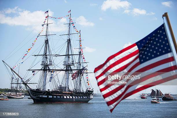 The USS Constitution made its way toward Charlestown In the foreground is a flag on the USCG CGC Escanaba The USS Constitution made its 17gun salute...