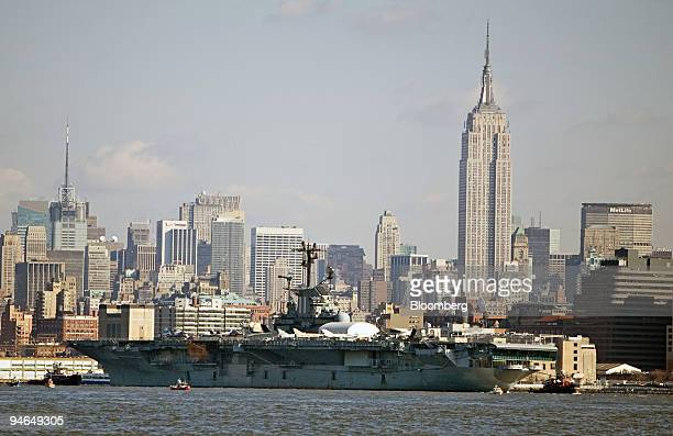 The USS Intrepid a World War II aircraft carrier is towed down the Hudson River past the Empire State building in the background as seen from Liberty...