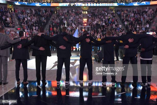 The Utah Jazz lock arms during the National Anthem prior to their game against the Denver Nuggets at Vivint Smart Home Arena on October 18 2017 in...