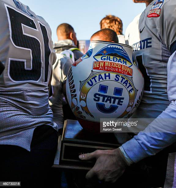 The Utah State Aggies protect the Gildan New Mexico Bowl Trophy after having just defeated the UTEP Miners at the New Mexico University Stadium on...